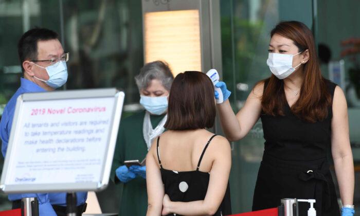 Los gerentes de los edificios realizan controles de temperatura fuera de un edificio en el distrito financiero de Singapur el 10 de febrero de 2020. (Roslan Rahan / AFP a través de Getty Images)