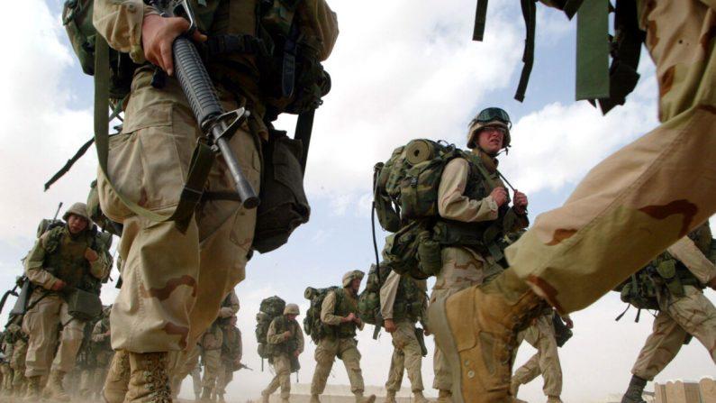 Los marines estadounidenses de la 1a División de Infantería de Marina regresan de una marcha de seis millas cerca de la frontera iraquí en Kuwait el 15 de febrero de 2003. (Joe Raedle / Getty Images)