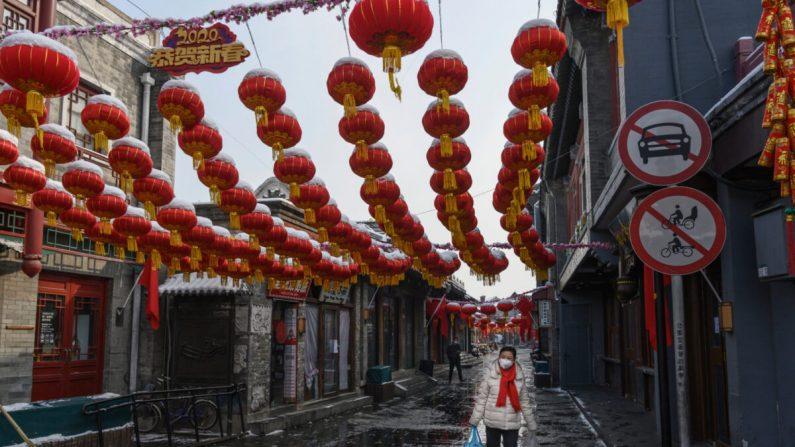 Una mujer china usa una máscara protectora mientras camina en una calle comercial casi vacía y cerrada en Beijing, China, el 7 de febrero de 2020. (Kevin Frayer/Getty Images)