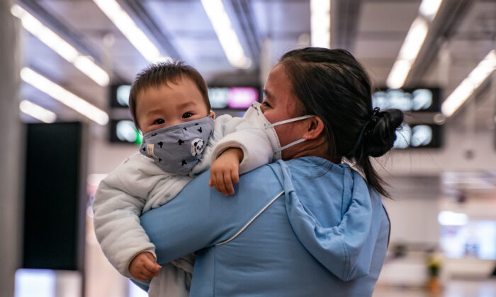 Una mujer y su bebé usan una mascarilla protectora al salir de la estación de tren de alta velocidad de Hong Kong, el 29 de enero de 2020. (Anthony Kwan/Getty Images)