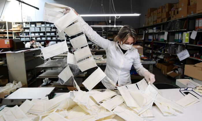 Un empleado controla las máscaras quirúrgicas en un taller de cuero convertido en una fábrica de máscaras, cerca de Vigevano, Lombardía, Italia, el 19 de marzo de 2020. (Miguel Medina/AFP vía Getty Images)