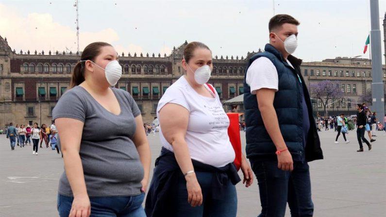 Un grupo de personas usa cubre bocas en una de las principales calles de Ciudad de México. EFE/José Pazos/Archivo