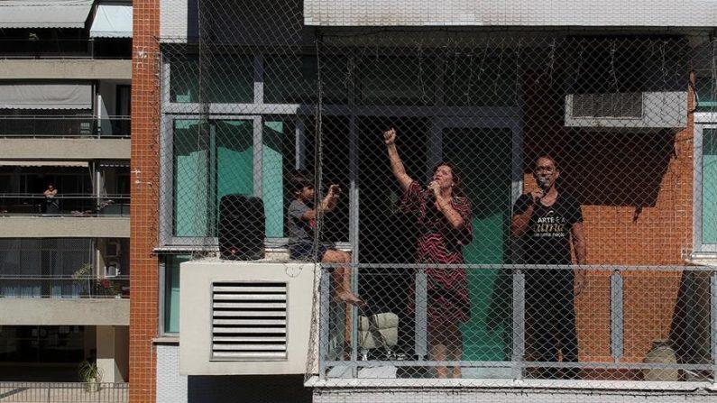 Una pareja de cantantes de ópera del Teatro Municipal convirtió la ventana del apartamento en el que viven en un escenario para cantarle a sus vecinos y darles algunos minutos de alegría en tiempos de confinamiento por la pandemia del coronavirus, este miércoles, en Río de Janeiro (Brasil). EFE/ Antonio Lacerda