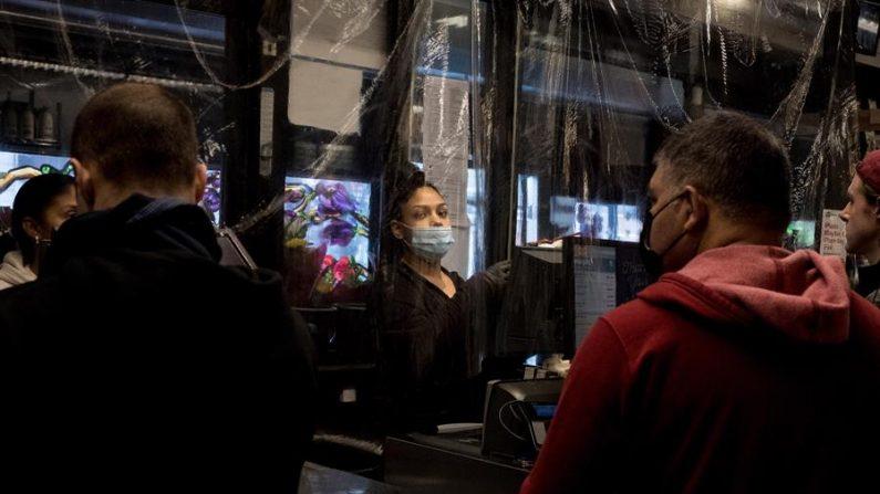 El personal del supermercado trabaja detrás de una cortina de plástico mientras atiende a los clientes en Brooklyn, Nueva York, EE.UU., 24 de marzo de 2020. EFE/EPA/Alba Vigaray