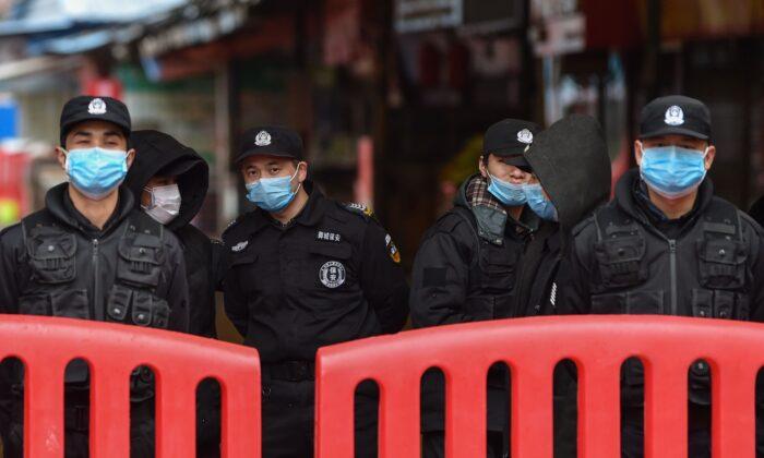 El 24 de enero de 2020, oficiales de policía y guardias de seguridad se encuentran frente al mercado mayorista de mariscos de Huanan en Wuhan. (HECTOR RETAMAL / AFP a través de Getty Images)