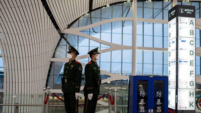Foto tomada el 14 de febrero de 2020 donde se muestra a policías paramilitares chinos con máscaras protectoras mientras vigilan un área en el aeropuerto internacional de Daxing en Beijing. (Nicolas Asfouri/AFP a través de Getty Images)