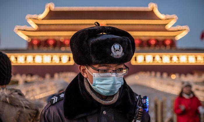 Un policía con una máscara protectora pasa por delante del retrato del difunto dictador comunista Mao Zedong (no aparece en la foto) en la Puerta de Tiananmen en Beijing el 23 de enero de 2020. (NICOLAS ASFOURI/AFP vía Getty Images)