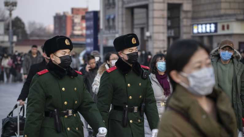 Los policías chinos usan máscaras protectoras mientras patrullan en la estación de Beijing antes del Festival de Primavera anual el 22 de enero de 2020 en Beijing. (Kevin Frayer/Getty Images)