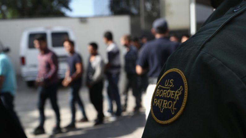 Inmigrantes ilegales abandonan un tribunal federal de Estados Unidos con grilletes en McAllen, Texas, el 11 de junio de 2018. (John Moore/Getty Images)