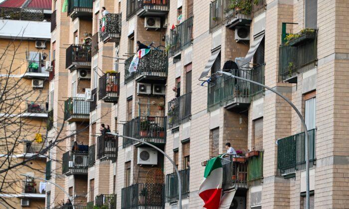 """Las personas agitan y aplauden junto a las banderas italianas, durante un flash mob """"Una canzone per l'Italia"""" (Una canción para Italia) en el distrito de Magliana en Roma el 15 de marzo de 2020. (Andreas Solaro/AFP/Getty Images)"""