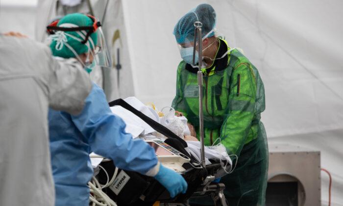 Un paciente es tratado por un médico en el Hospital de Campo de Emergencia de Samaritan's Purse, en Cremona, cerca de Milán, Italia, el 20 de marzo de 2020. (Emanuele Cremaschi/Getty Images)