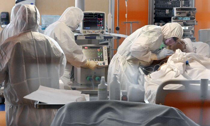 Un trabajador médico con equipo de protección (dcha.) atiende a un paciente en la nueva unidad de cuidados intensivos de nivel 3 para casos de COVID-19 en el hospital Casal Palocco cerca de Roma, Italia, el 24 de marzo de 2020. (Alberto Pizzoli/ AFP vía Getty Images)