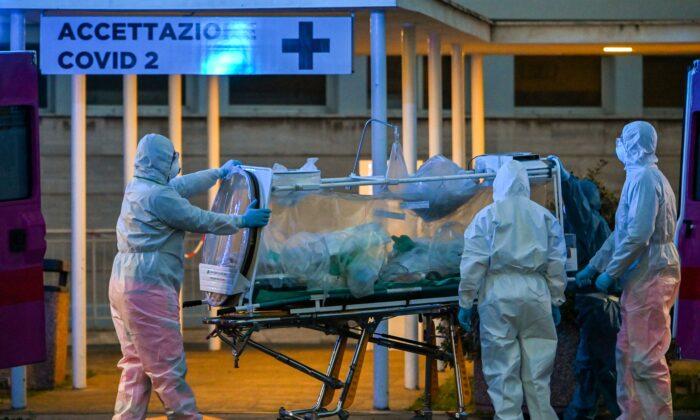 Trabajadores médicos en overol llevan a un paciente en cuidados intensivos al recién construido hospital temporal Columbus Covid 2 para combatir la nueva infección de coronavirus, en el hospital Gemelli de Roma, el 16 de marzo de 2020. (Andreas Solaro /AFP vía Getty Images)