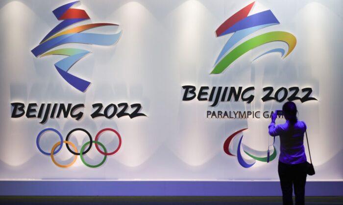 Un visitante toma fotos de los logotipos de los próximos Juegos Olímpicos y Paralímpicos de Invierno de Beijing 2022 durante la Exposición Olímpica de Beijing, en Beijing el 8 de agosto de 2018. (Wang Zhao/AFP a través de Getty Images)