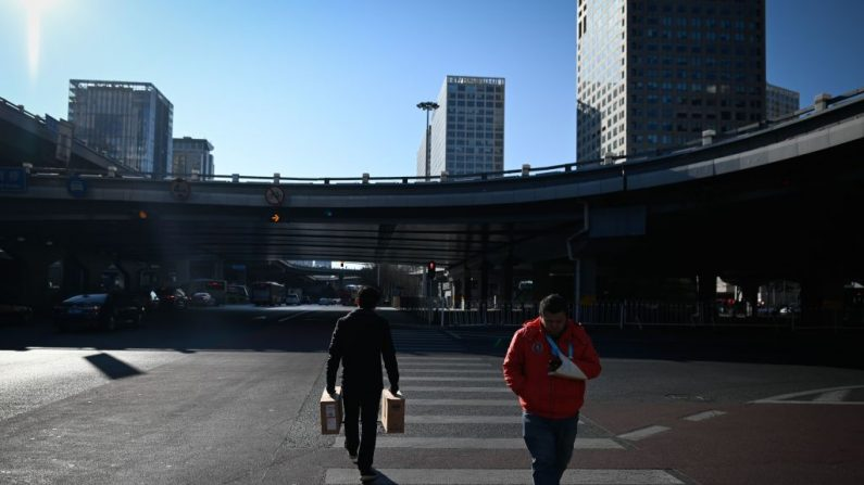 Los peatones cruzan una calle en un Distrito Comercial Central (CBD) en Beijing el 14 de enero de 2020. (Wang Zhao / AFP a través de Getty Images)