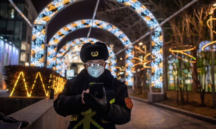 Un guardia de seguridad lleva una mascarilla para protegerse del virus del PCCh, que causa la enfermedad de COVID-19, mientras navega con su teléfono móvil en la entrada de un centro comercial casi vacío en Beijing, el 27 de febrero de 2020. (NICOLAS ASFOURI/AFP vía Getty Images)