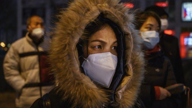 Oficinistas chinos usan máscaras protectoras cuando hacen fila para el autobús después de salir del trabajo en Beijing, China, el 2 de marzo de 2020. (Kevin Frayer/Getty Images)