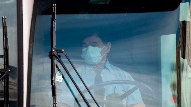 Un conductor de autobús lleva una máscara facial en el área de Flushing de Queens el 2 de marzo de 2020 en la Ciudad de Nueva York. (Foto de Johannes EISELE / AFP) (Foto de JOHANNES EISELE/AFP a través de Getty Images)