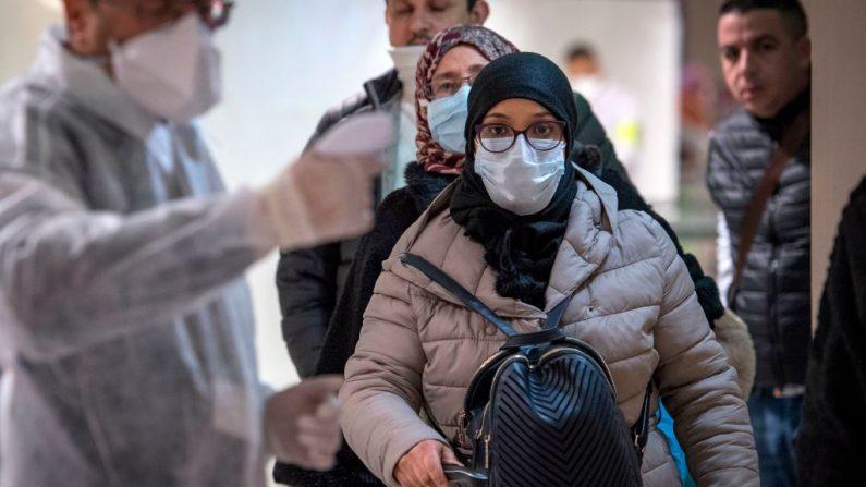 Trabajadores sanitarios marroquíes escanean a los pasajeros que llegan de Italia para detectar el coronavirus COVID-19 en el aeropuerto internacional Mohammed V de Casablanca el 3 de marzo de 2020. (Foto de FADEL SENNA/AFP vía Getty Images)