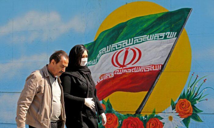 Los iraníes con máscaras pasan junto a un mural que muestra su bandera nacional en Teherán, el 4 de marzo de 2020. (Atta Kenare/AFP a través de Getty Images)