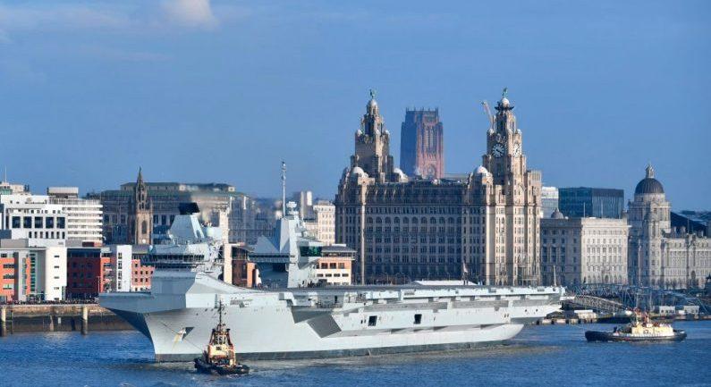 Remolcadores maniobran el HMS Príncipe de Gales de la Marina Real Británica, mientras se prepara para abandonar los muelles de Liverpool, al noroeste de Inglaterra, el 6 de marzo de 2020. (PAUL ELLIS/AFP vía Getty Images)