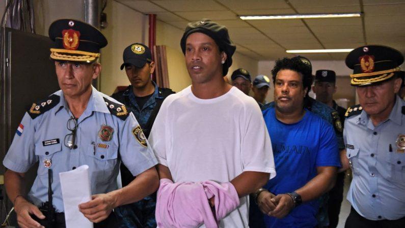 El exjugador de fútbol brasileño Ronaldinho (c) y su hermano Roberto Assis (d) llegan al Palacio de Justicia de Asunción para comparecer ante un fiscal después de su entrada irregular al país, en Asunción (Paraguay), en 7 de marzo de 2020. (NORBERTO DUARTE / AFP / Getty Images)