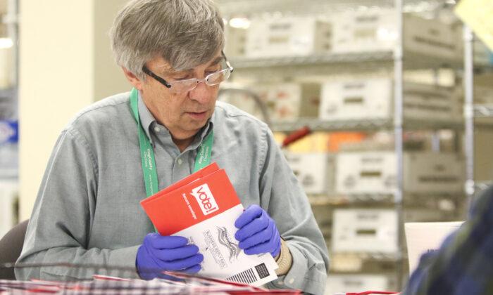Los trabajadores electorales clasifican las boletas de votación por correo para las primarias presidenciales, en las elecciones del condado de King, en Renton, Washington, el 10 de marzo de 2020. (JASON REDMOND/AFP a través de Getty Images)
