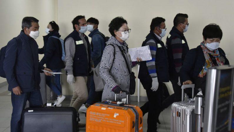 Los pasajeros que llegan al aeropuerto internacional de El Alto llevan máscaras faciales de protección en un intento de prevenir la propagación del virus del PCCh, en El Alto, Bolivia, el 11 de marzo de 2020. (AIZAR RALDES/AFP vía Getty Images)