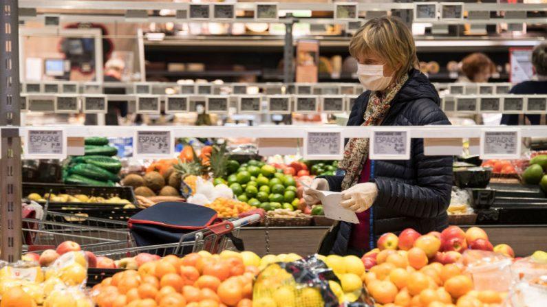 Una mujer con una máscara facial compra fruta en un supermercado el 16 de marzo de 2020, durante el virus del PCCh (SEBASTIEN BOZON/AFP/Getty Images)