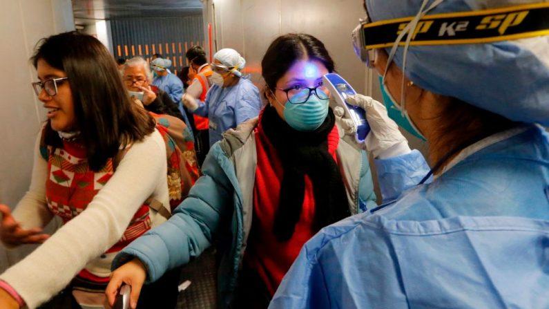 El personal médico comprueba la temperatura del viajero al desembarcar a su llegada al aeropuerto internacional Jorge Chávez en Callao, Lima, Perú, el 16 de marzo de 2020, en el último vuelo desde EE.UU. antes de que se cierren las fronteras. (LUKA GONZALES/AFP vía Getty Images)