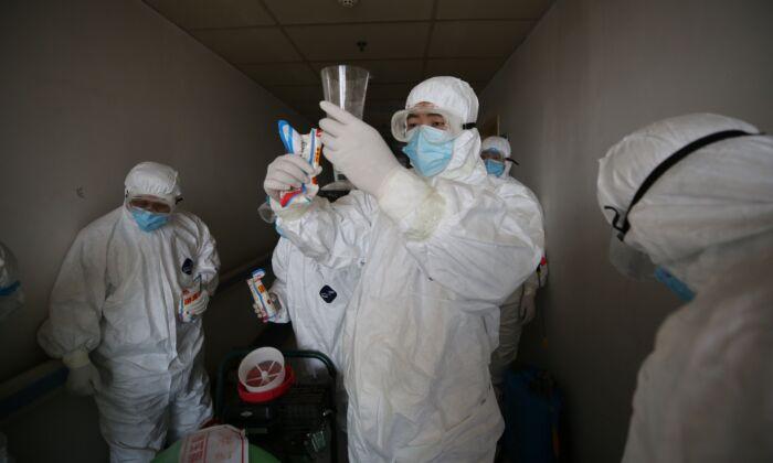 Los trabajadores se preparan para desinfectar las habitaciones del hospital de la Cruz Roja en Wuhan, China, el 18 de marzo de 2020. (STR/AFP vía Getty Images)