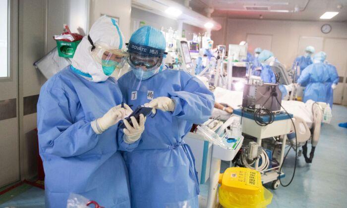 Personal médico revisa un teléfono móvil mientras tratan a pacientes con el virus del PCCh en un hospital de Wuhan, China, el 19 de marzo de 2020. (STR/AFP vía Getty Images)