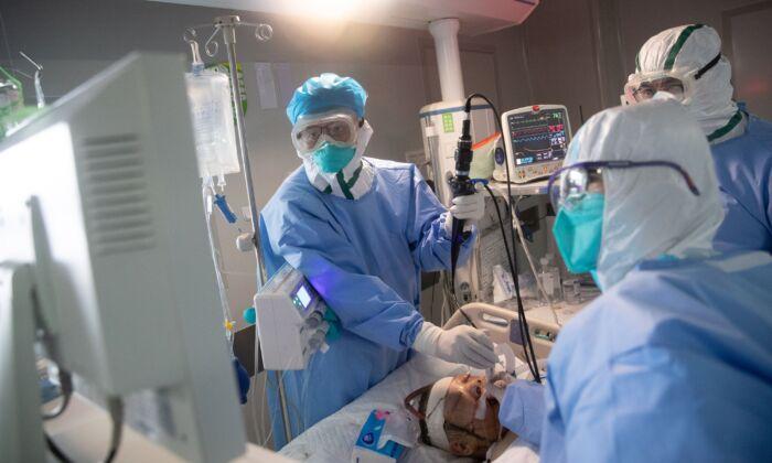 El personal médico trata a pacientes con COVID-19 en un hospital de Wuhan, China, el 19 de marzo de 2020. (STR/AFP a través de Getty Images)
