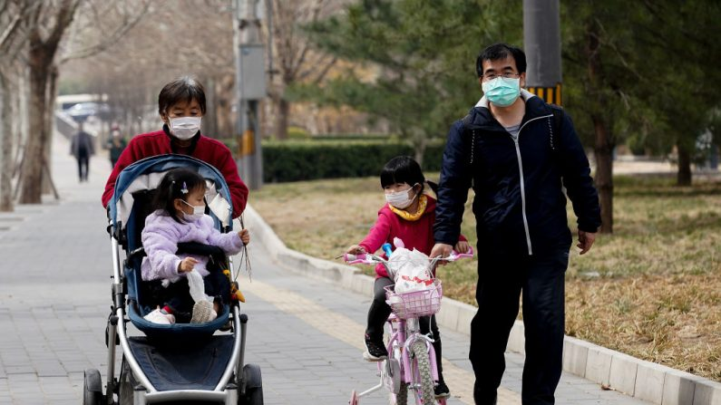 Una familia china con una máscara protectora en un parque en Beijing, China, el 19 de marzo de 2020. (Lintao Zhang/Getty Images)