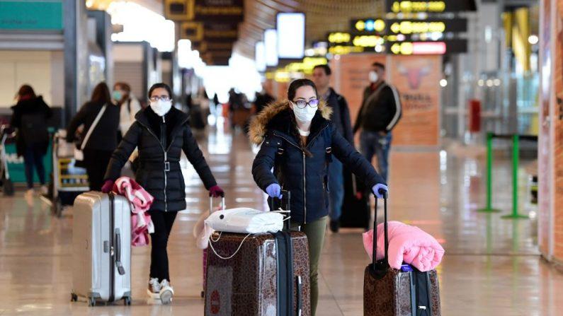 Los pasajeros que llevan mascarillas y guantes como medida preventiva para el covid-19 empujan los carros en el aeropuerto Adolfo Suárez de Barajas, España, el 20 de marzo de 2020. (JAVIER SORIANO/AFP vía Getty Images)
