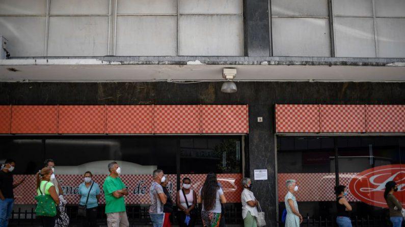 Personas usa máscaras faciales como medida preventiva contra la propagación del virus del PCCh, mientras hacen fila para comprar alimentos fuera de un supermercado en el barrio de Chacao en Caracas, Venezuela, el 20 de marzo de 2020. (FEDERICO PARRA/AFP vía Getty Images)