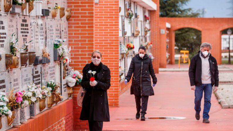 Personas con máscaras llegan al cementerio Municipal Sur de Madrid, el 23 de marzo de 2020, para asistir al entierro de un hombre que murió del virus del PCCh. (BALDESCA SAMPER/AFP vía Getty Images)