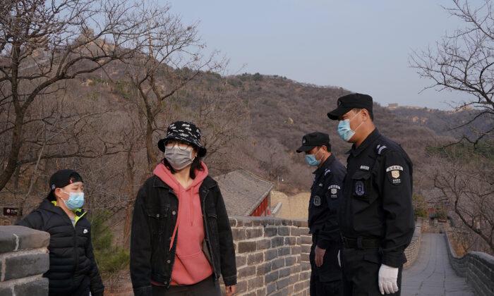 Dos guardias de seguridad usan una máscara protectora en la, casi vacía, Gran Muralla de Badaling, el 24 de marzo de 2020, en Beijing, China. (Lintao Zhang/Getty)
