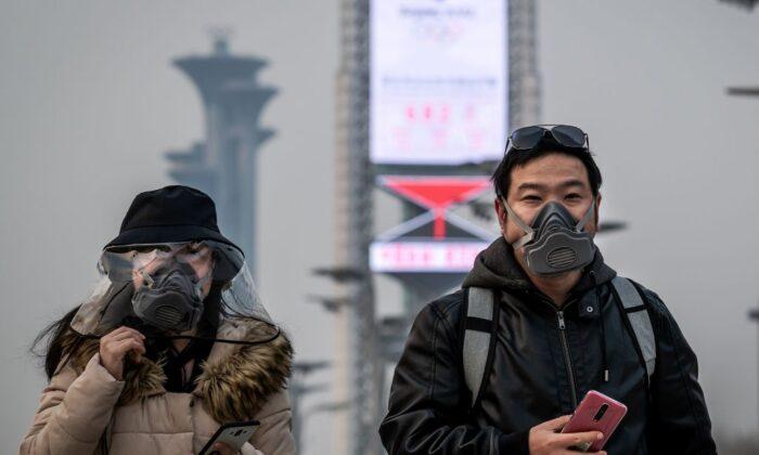Personas con máscaras faciales caminan por el parque olímpico de Beijing el 24 de marzo de 2020. (Nicolas Asfouri/AFP a través de Getty Images)
