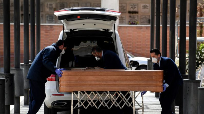 Imagen ilustrativa. Empleados de funeraria con máscaras faciales llevan un ataúd al crematorio el 24 de marzo de 2020 durante el funeral de una víctima de COVID-19. (OSCAR DEL POZO / AFP a través de Getty Images)