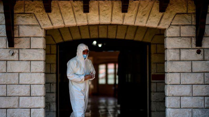 Un empleado de la municipalidad de La Plata con un traje protector sale de una habitación donde los pacientes con el virus del PCCh serán aislados en el parque de diversiones de la República de los Niños en La Plata, Argentina, el 24 de marzo de 2020. (RONALDO SCHEMIDT/AFP vía Getty Images)