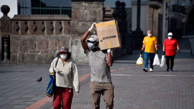 La gente lleva provisiones mientras camina por el centro histórico de Quito, Ecuador, el 25 de marzo de 2020 durante la pandemia del virus del PCCh. (RODRIGO BUENDIA/AFP vía Getty Images)