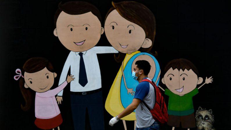 Un hombre lleva una mascarilla y guantes como medida preventiva contra la propagación del virus del PCCh, mientras pasa por delante de un mural en Bogotá, Colombia, el 25 de marzo de 2020. (JUAN BARRETO/AFP vía Getty Images)