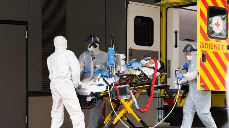 Los médicos atienden a un paciente infectado por el virus del PCCh a su llegada de Italia al hospital universitario para su tratamiento posterior el 26 de marzo de 2020 en Dresde, Alemania oriental. (MATTHIAS RIETSCHEL/POOL/AFP vía Getty Images)