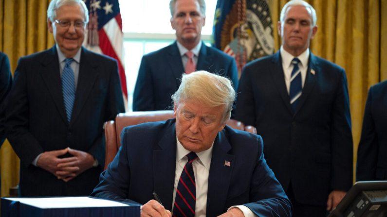El presidente de los Estados Unidos, Donald Trump, firma la ley CARES, un paquete de rescate de USD 2 billones para proporcionar alivio económico en medio del brote de coronavirus, en la Oficina Oval de la Casa Blanca el 27 de marzo de 2020. (JIM WATSON/AFP a través de Getty Images)