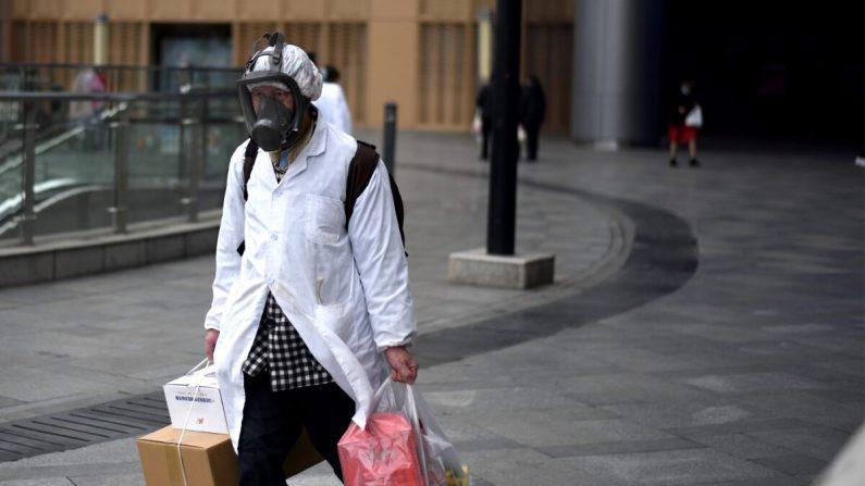 Un hombre con una máscara lleva artículos que compró en un supermercado en Wuhan, China, el 30 de marzo de 2020. (NOEL CELIS/AFP a través de Getty Images)