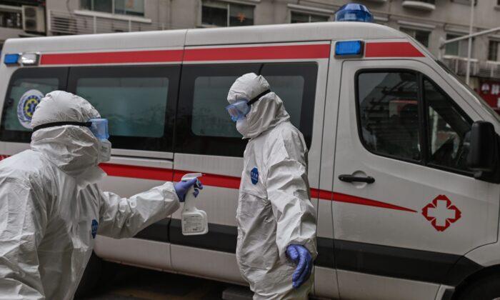 Personal médico de una ambulancia rocía desinfectante sobre su colega luego de llevar a un paciente que había sido recientemente curado del virus del PCCh, en el Hospital Cruz Roja en Wuhan, China el 30 de marzo de 2020. (HECTOR RETAMAL/AFP via Getty Images)