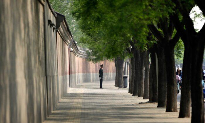 Un soldado vigila junto a un muro rojo en las afueras del complejo de liderazgo de Zhongnanhai en Beijing el 6 de mayo de 2013. (Getty Images/ Jason Lee/AFP)