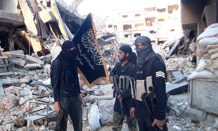 Terroristas del grupo de Al-Qaeda en el Levante, el Frente de Al-Nusra, se encuentran entre los edificios destruidos cerca de la línea del frente con soldados del gobierno sirio en un campo de refugiados palestinos de Yarmuk al sur de Damasco el 22 de septiembre de 2014. (Rami Al-Sayed/AFP/Getty Images)