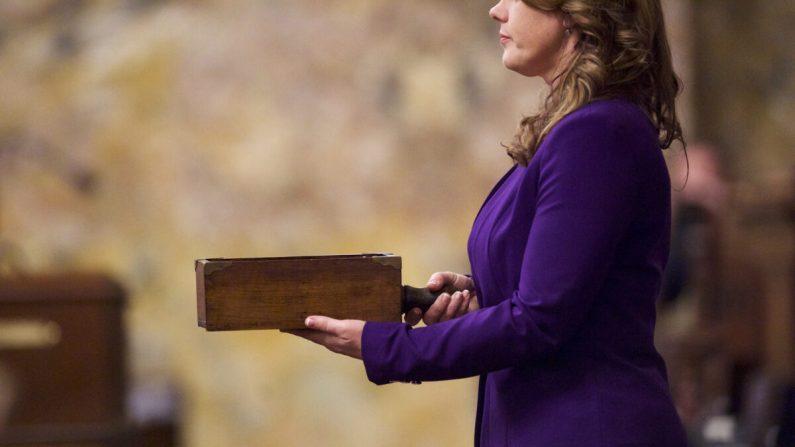 Una asistente sostiene la urna antes de que los electores emitan su voto en la cámara de la Cámara de Representantes dentro del edificio del Capitolio de Pensilvania en Harrisburg, Pennsylvania, el 19 de diciembre de 2016. (Mark Makela/Getty Images)